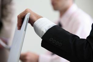 膝に乗せたノートパソコンをあける男性の手元の写真素材 [FYI03231539]