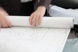 図面を丸める女性の手元の写真素材 [FYI03231553]