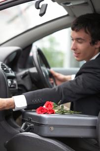 ビジネスバックに置いたバラの花と外国人男性の写真素材 [FYI03231642]