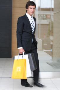 ビジネスバックとペーパーバックを持って歩く男性の写真素材 [FYI03231659]