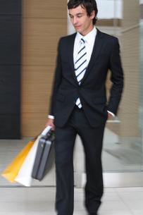 ビジネスバックとペーパーバックを持って歩く男性の写真素材 [FYI03231660]