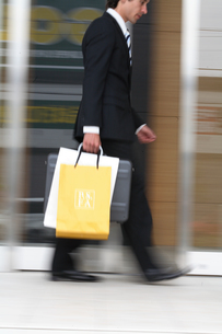 ビジネスバックとペーパーバックを持って歩く男性の写真素材 [FYI03231662]