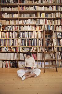 本棚の前で本を読む外国人女性の写真素材 [FYI03231758]