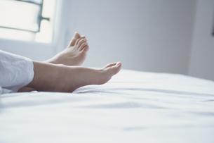 白いシーツの上の女性の素足の写真素材 [FYI03231775]
