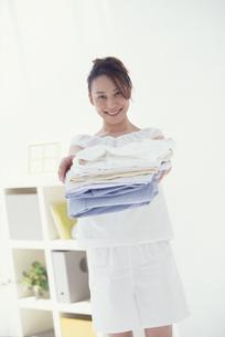 たたんだシャツを差し出す女性の写真素材 [FYI03231793]