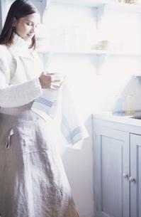 食器をクロスで拭く女性の写真素材 [FYI03231811]