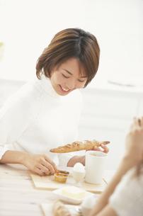 ダイニングテーブルで朝食を摂る女性の写真素材 [FYI03231812]