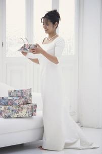 ソファの上のギフトボックスを開ける花嫁の写真素材 [FYI03231903]