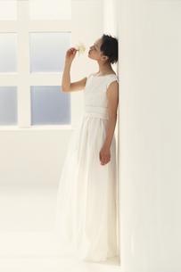 壁にもたれて花の香りをかぐ花嫁の写真素材 [FYI03231915]