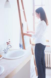 洗面所でタオルをかける女性の写真素材 [FYI03231919]