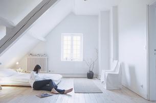 ベットルームの床に横たわった女性の写真素材 [FYI03231925]