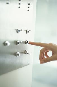 壁面のスイッチに触れる女性の指先の写真素材 [FYI03231935]