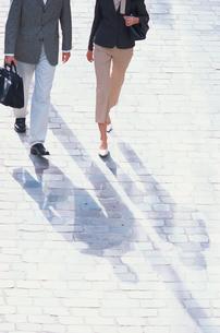 石畳の道を歩くビジネススタイルの男女の写真素材 [FYI03231947]