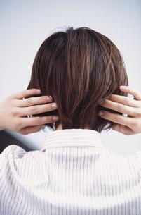 両手で髪に触れる女性の後姿の写真素材 [FYI03231973]