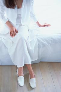 白い服を着てベットに座った女性の写真素材 [FYI03231982]