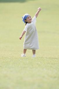 青いバンダナを巻き腕を広げた少女の写真素材 [FYI03232027]