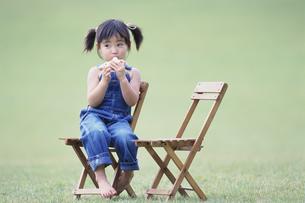 椅子に座ってオカリナを吹く少女の写真素材 [FYI03232035]