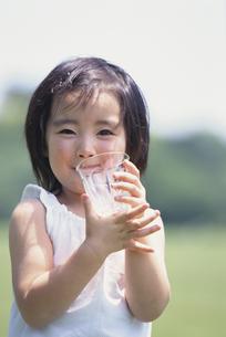 グラスに入った水を飲む少女の写真素材 [FYI03232042]