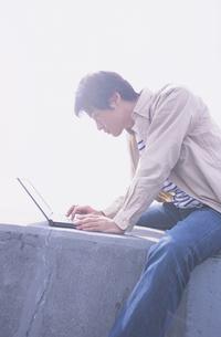 防波堤の上でノートパソコンをする男性の写真素材 [FYI03232077]