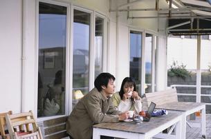 カフェテラスの並んで座ったカップルの写真素材 [FYI03232086]