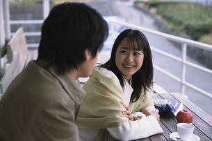 カフェテラスで並んで座ったカップルの写真素材 [FYI03232087]