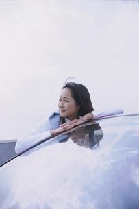 車のフロントガラスにもたれた女性の写真素材 [FYI03232092]