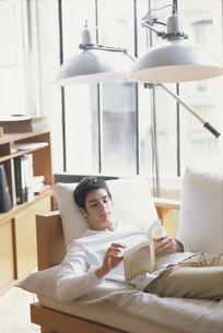 ソファに横になり本を読む男性の写真素材 [FYI03232159]