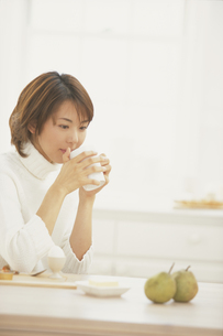 ダイニングテーブルでコーヒーを飲む女性の写真素材 [FYI03232162]