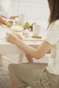 ダイニングテーブルで朝食をとる女性の写真素材 [FYI03232172]
