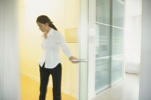 室内のドアを開ける女性の写真素材 [FYI03232177]