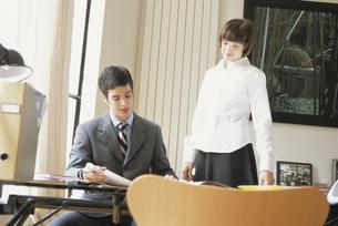 デスクに座る男性と脇に立つ女性の写真素材 [FYI03232193]