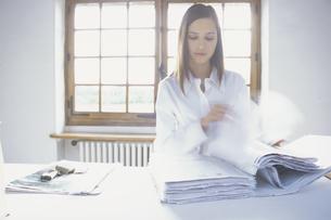 ファイルの書類をめくる女性の写真素材 [FYI03232195]
