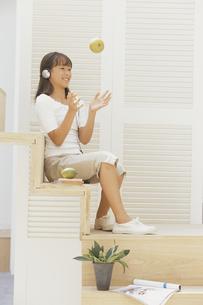 階段に座りリンゴを放る少女の写真素材 [FYI03232227]