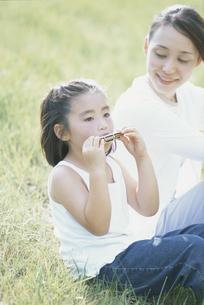 お母さんとハーモニカを吹く少女の写真素材 [FYI03232254]