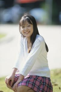 公園で座ったチェックのスカートの少女の写真素材 [FYI03232257]