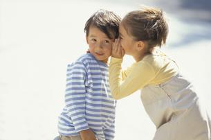 少年の耳元に手を当て話す少女の写真素材 [FYI03232259]