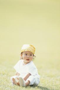 バンダナを巻き芝生に座った女児の写真素材 [FYI03232262]