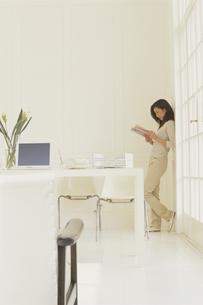 壁際で本を読む女性の写真素材 [FYI03232271]
