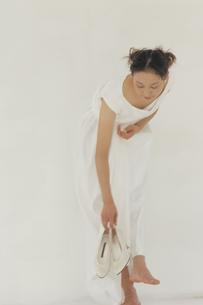 ハイヒールを拾うウェディングドレスの花嫁の写真素材 [FYI03232308]