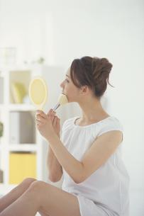 手鏡を見ながらメイクする女性の写真素材 [FYI03232315]