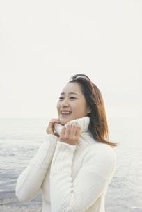 白いセーターを着て海辺に立つ女性の写真素材 [FYI03232328]