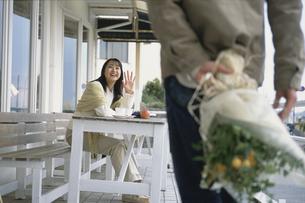 男性に手を振るカフェテラスの女性の写真素材 [FYI03232344]