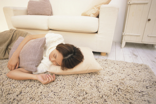 ソファの前の床で眠る女性の写真素材 [FYI03232358]