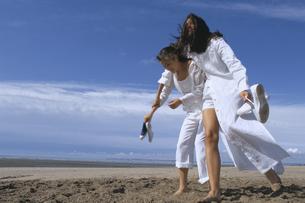 砂浜でふざけ合う女性2人の写真素材 [FYI03232371]