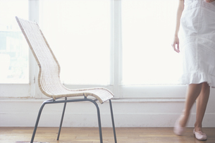 窓際の籐の椅子と女性の写真素材 [FYI03232394]
