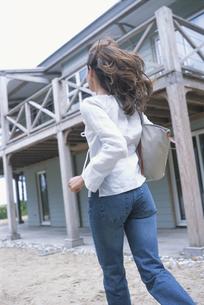 バッグを肩に掛け走る女性の後姿の写真素材 [FYI03232410]