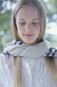 首にストールを巻いて目を閉じる女性の写真素材 [FYI03232524]