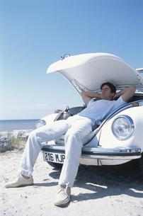 車のボンネットを開けて休む男性の写真素材 [FYI03232539]