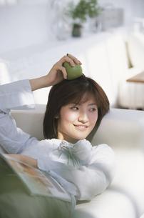 横になって頭に洋梨をのせる女性の写真素材 [FYI03232615]