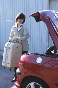 スーツケースを車のトランクに入れる女性の写真素材 [FYI03232634]